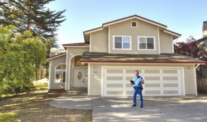 Picture of a home inspector by a new home
